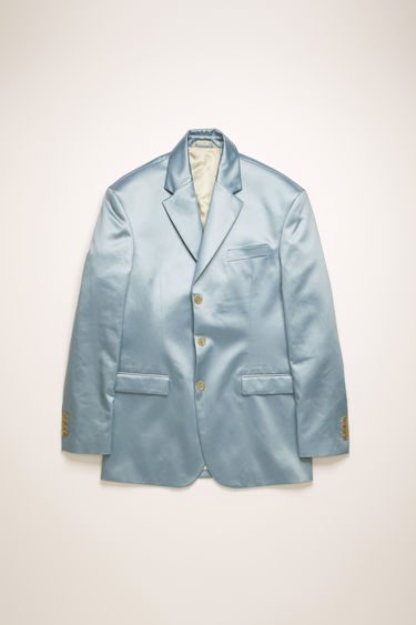 Acne Studios powder blue suit jacket is crafted from cotton-blend that has a lustrous satin finish, then finished with a coordinating buttoned belt at the back.