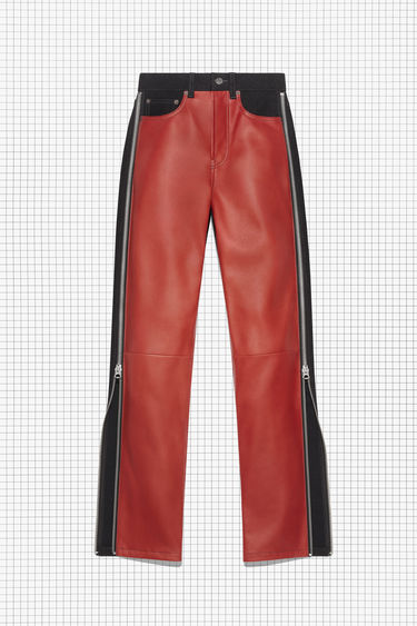 Acne Studios Repurposed black/red panel trousers are made of rigid black denim and red leather, featuring zipper details on both legs. They fit high on the waist with straight legs.