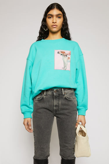 Acne Studios turquoise sweatshirt is crafted from organic cotton to a relaxed silhouette with dropped shoulders and adorned with a printed patch, featuring a prize dog created by Britsh artist Lydia Blakeley.