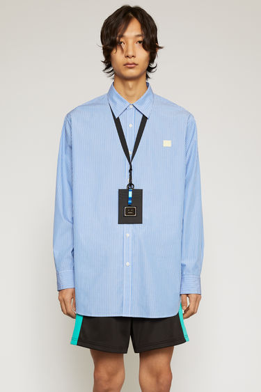 Acne Studios blue/white striped shirt is crafted from organic cotton to a boxy shape with an oversized fit and finished with a button-down front closure and face-embroidered patch on the chest.