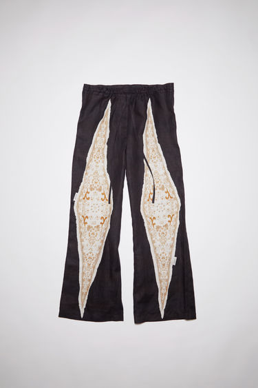 Acne Studios black/white linen trousers are cut for a relaxed fit with straight legs and a drawstring waist featuring a bandana print on both legs.