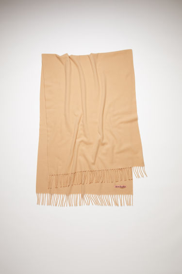 Acne Studios camel brown oversized fringed scarf is made of pure wool, featuring a label in one corner.