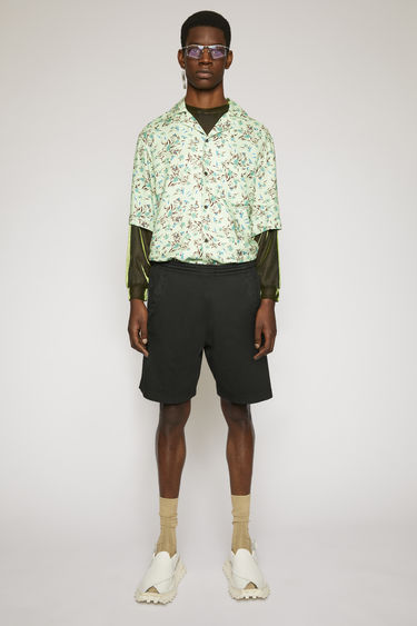 Acne Studios black shorts are made from brushed cotton jersey that's been garment dyed for a soft, washed-out finish and features a reversed logo purposely printed imprecisely across the left side.