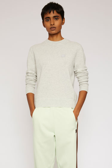 Acne Studios light grey melange sweater is finely knitted from pure wool and finished with a tonal face-embroidered patch and ribbed trims.