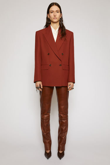Acne Studios rust brown suit jacket is constructed to a slightly oversized, boxy shape and has lightly padded shoulders, peak lapels and a double-breasted front.