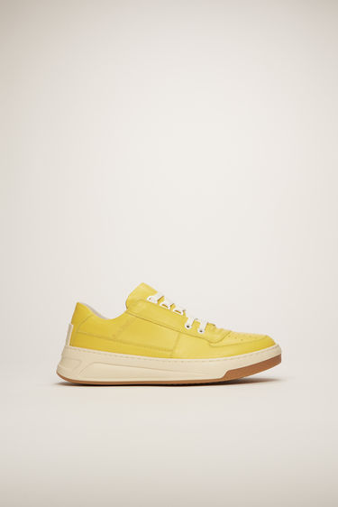 Acne Studios Steffey Lace Up yellow/white sneakers are crafted from smooth calf leather and shaped to a round toe with a low-top silhouette.