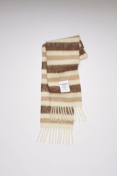 Acne Studios white/beige/brown striped scarf is spun from a blend of alpaca, wool and mohair yarns in a relaxed long-length silhouette that drapes through the body. It's finished with a soft, brushed texture and a logo patch above the fringed edges.