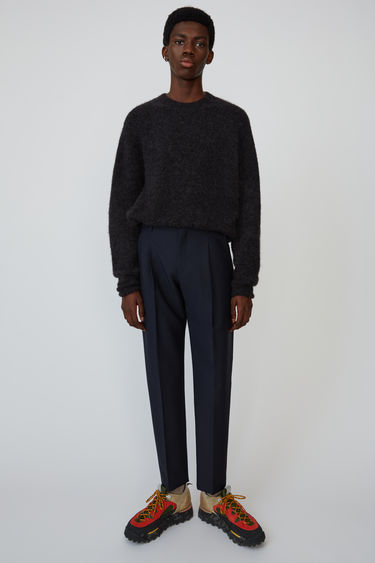 Acne Studios navy trousers are crafted from wool-blend suiting and shaped to a tapered silhouette with a pleated front.