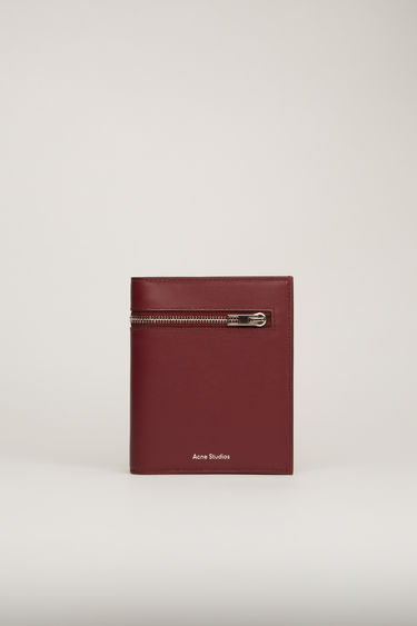 Acne Studios burgundy trifold wallet is crafted with five card slots, three receipt partitions and two zipped pockets from grained leather and accented with a silver-tone metal zip across the front.