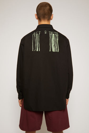 Acne Studios black shirt is made from cotton and linen to an oversized silhouette and embroidered 'Act on Truth' in bold letters across the back with fringed trims.