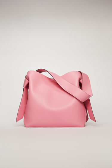 Acne Studios Musubi Midi pink/black bag features twisted knots inspired by the formation of traditional Japanese obi sash. It's crafted from soft grain leather and has a central zipped divider to store small essentials.