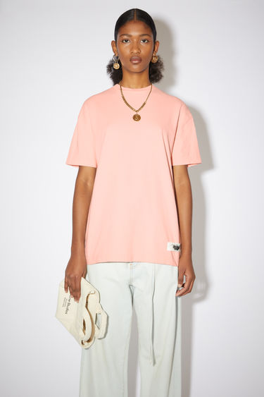 Acne Studios salmon pink crew neck t-shirt is made of organic cotton with an Acne Studios label on the lower front.
