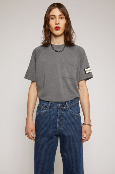 Acne Studios graphite grey t-shirt is crafted from midweight loopback jersey and shaped to a relaxed silhouette with a round neckline and raglan sleeves. It features a patch pocket and a reversed label patch on left sleeve.