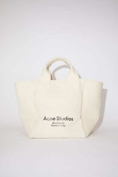 Acne Studios beige large shopper bag is made of thick cotton canvas with Acne Studios branding on the front.