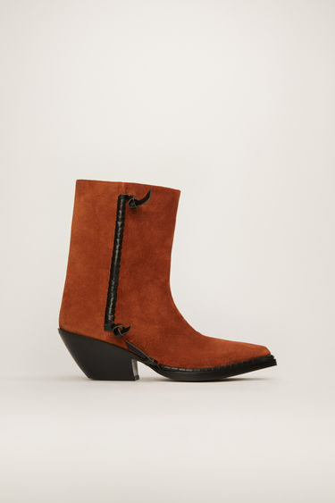 Acne Studios rust brown boots offer a contemporary take on the traditional cowboy boots. Crafted from suede, they rest on a slanted stacked heel and are accented with leather knots and whipstitched seams.