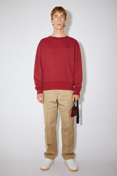 Acne Studios deep red crew neck sweatshirt is made of organic cotton with a face logo patch and ribbed details.