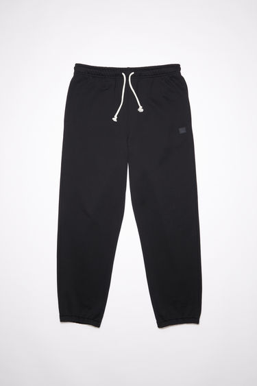 Acne Studios black organic cotton sweatpants feature an elastic drawstring waist and tonal embroidered face patch on the front.