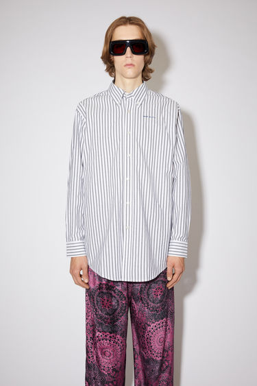 Acne Studios midnight blue long sleeve shirt is made of striped cotton with a logo at the chest.