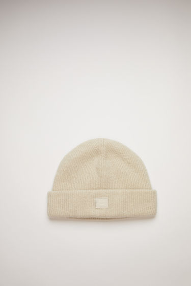 Acne Studios cream beige beanie is knitted with wool and lycra for a closer fit and accented with a tonal face-embroidered patch on front.
