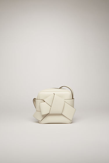 Acne Studios Musubi Camera white/sand beige is a camera-style bag with knot detail based on the traditional Japanese obi sash.