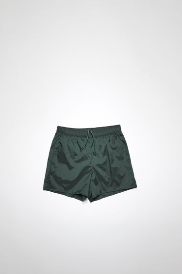 Acne Studios forest green swim shorts are crafted from technical nylon with front and back pockets and finished with an elasticated waistband with round drawstrings.