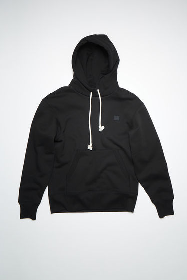Acne Studios black regular fit hooded sweatshirt is made of organic cotton with an embroidered face and ribbed details.