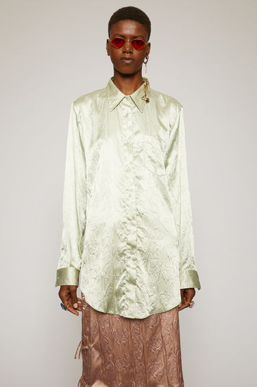 Acne Studios pastel green satin shirt is cut to a relaxed fit with a curved shirttail hem and features an embossed floral pattern.