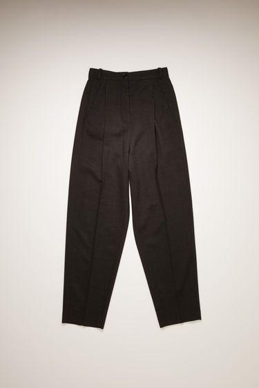 Acne Studios charcoal grey trousers are tailored in a tapered-leg shape with a low dropped crotch and features pleats at the front of the waist.