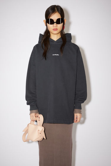 Acne Studios black hooded sweatshirt is made of cotton with an Acne Studios logo at the centre chest