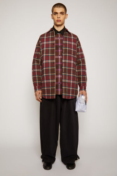 Acne Studios burgundy/beige padded overshirt is crafted from checked flannel quilted in a ripple pattern and has a point collar, chest patch pocket and two side welt pockets.