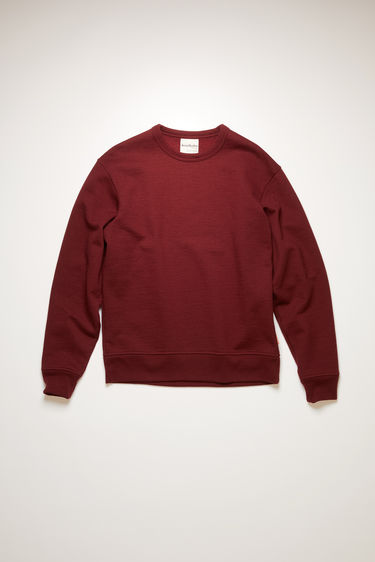 Acne Studios rosewood red sweatshirt is crafted from organically grown cotton and recycled polyester that's enzyme-washed for a soft handle and neatly finished with ribbed trims around the neckline, cuffs and hem.