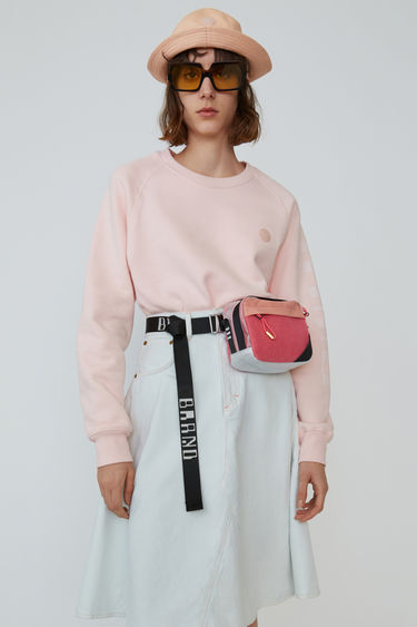Acne Studios Blå Konst blossom pink raglan sleeve sweatshirt with branding down one sleeve.