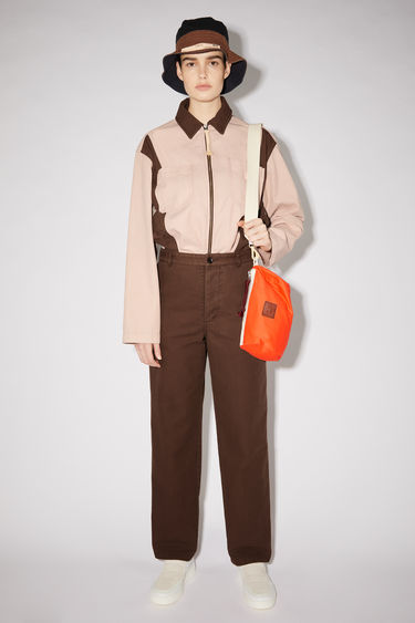 Acne Studios dark brown/powder pink workwear trousers are made of organic stonewashed cotton with a straight leg and contrasting pocket panels and a face patch.