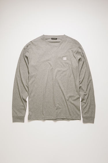Acne Studios light grey melange t-shirt is crafted from lightweight cotton jersey to a relaxed shape with a round neck and long sleeves and accented with a tonal face-embroidered patch on the chest.