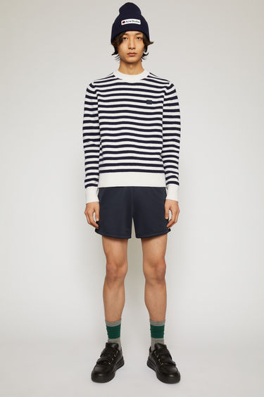 Acne Studios navy/white stripe sweater is knitted in a fine gauge from soft wool yarns and accented with a tonal face-embroidered patch on the chest.