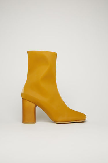 Acne Studios mustard yellow ankle boots are crafted from high-shine vinyl to a square-toe shape and set on a high block heel and durable rubber sole.