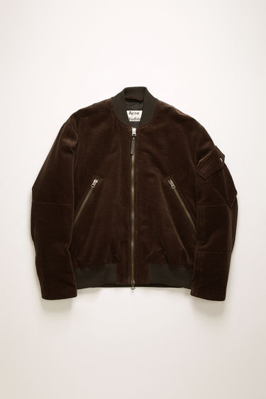 Acne Studios coffee brown bomber jacket is crafted from corduroy with padding and has an array of pockets on the bodice and sleeves.