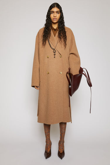 Acne Studios camel melange belted coat is crafted from double-faced wool to a relaxed silhouette and features peak lapels, dropped shoulders and a double-breasted front.