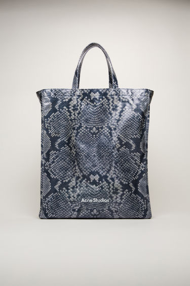 Acne Studios black/white tote bag is crafted from coated cotton for a glossy finish. It's patterned with a python print and features a white logo print across the front.