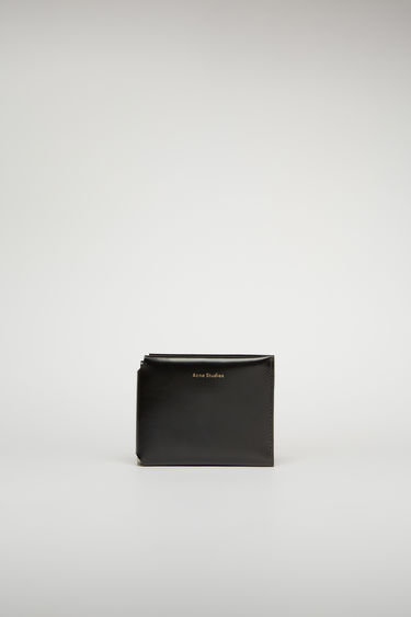 Acne Studios black trifold wallet is crafted from high-shine leather and completed with four card slots, a note compartment and a coin pocket.