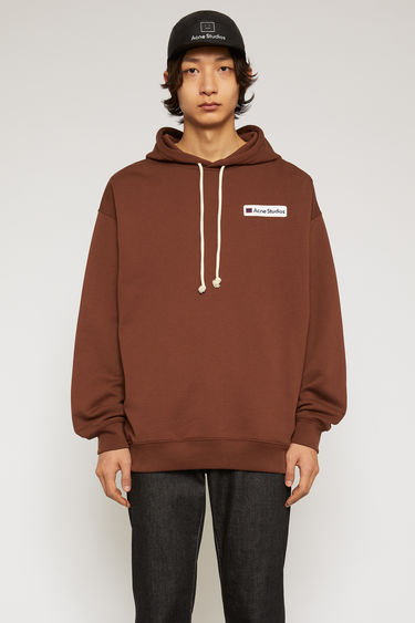 Acne Studios dark brown hooded sweatshirt is crafted from midweight loopback jersey to an oversized silhouette and accented with a logo-embroidered patch on the chest.