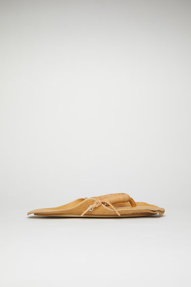 Acne Studios camel brown flip flop sandals are crafted from grain leather with rope-like straps and set on a padded footbed and a textured rubber sole. They're purposefully finished with raw edges for a DIY slant.