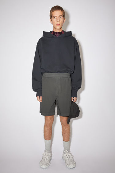 Acne Studios anthracite grey loose-fitting shorts are made of cotton with a logo at the back welt pocket.