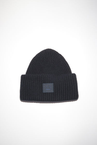 Acne Studios black beanie is rib-knitted from soft wool and accented with a face-embroidered patch on the front.