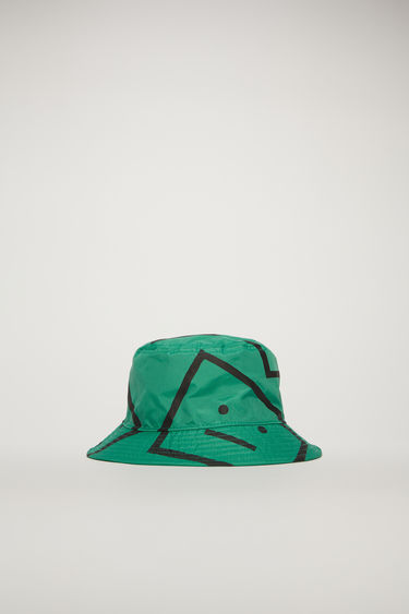 Acne Studios emerald green bucket hat is patterned with a face-motif print and features a flat-topped crown and a quilted brim.