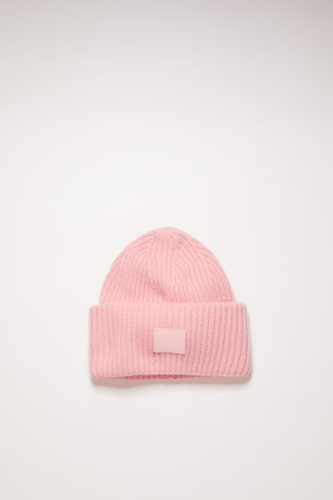 Acne Studios blush pink beanie is rib-knitted from soft wool and accented with a face-embroidered patch on the front.
