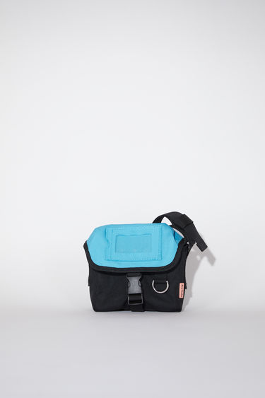 Acne Studios black/blue durable small messenger bag has an adjustable hard plastic buckle closure and Acne Studios logo tab.