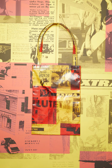 Acne Studios yellow/red oilcloth tote bag features a Stockholm Syndrome newspaper print.
