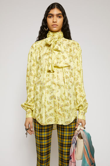 Acne Studios yellow/multi blouse is crafted from lightweight viscose that's printed with paisley motifs. It's cut to a fluid drape with a tie at the neck and finished with a curved hemline.