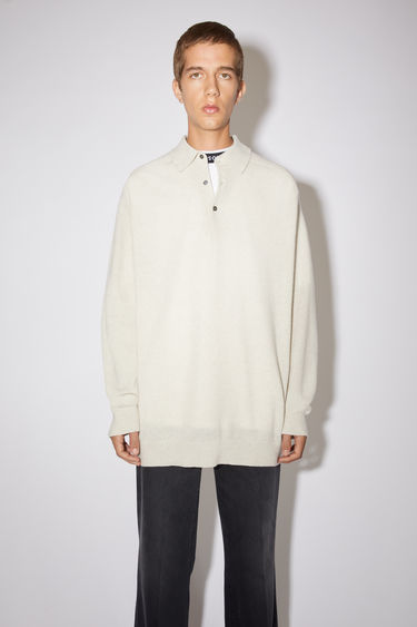 Acne Studios cold beige long sleeve polo sweater is made of lambswool with rib knit details at the cuffs and hem.